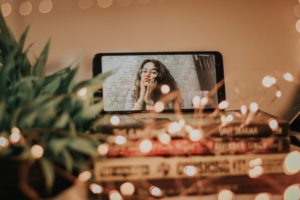 Woman on FaceTime with string lights surrounding phone