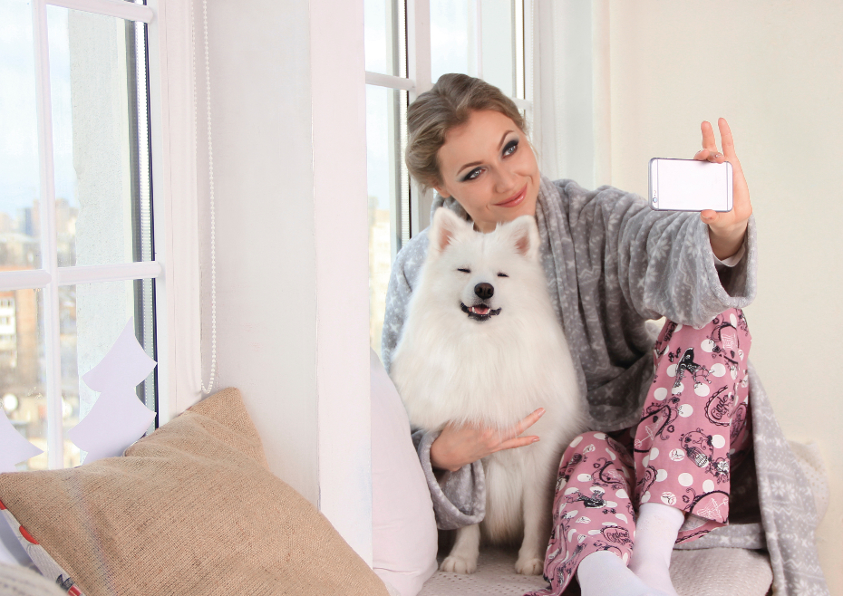 girl poses with white phone at home with pomeranian dog