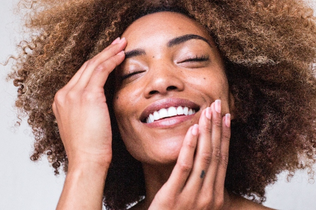 black woman rubs face and skin