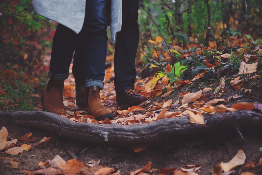 a couple walks through leaves in the woods or forest