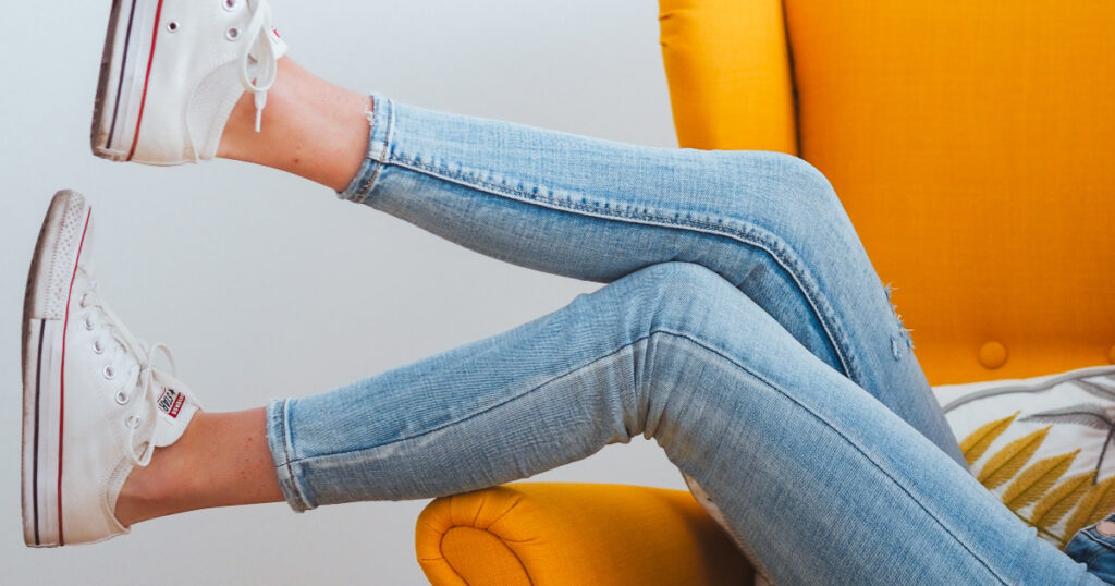 Girl wears light skinny jeans and white converse all-star shoes while sitting on a yellow chair