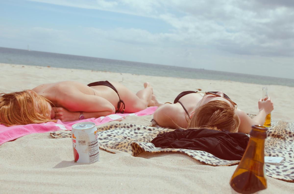 two girls lie in bikini bathingsuits on the sand on the beach