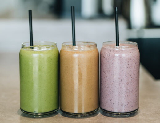 green, orange and purple smoothie drinks with straws