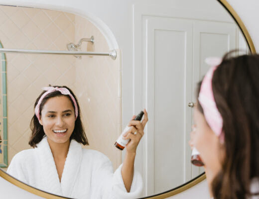 girl stands in front of mirror in a robe spraying on part of her skincare routine